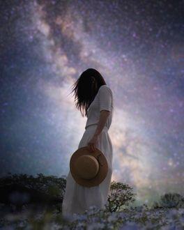 Фото Девушка со шляпой в руке стоит на фоне звездного неба