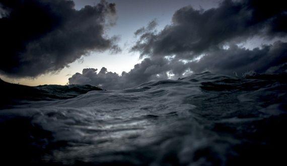 Фото Снимок моря которое на горизонте сливается с облаками