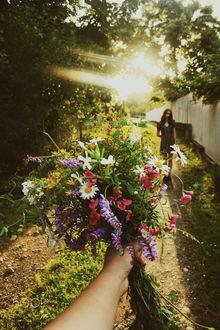 Фото Парень с цветами протянул руку навстречу девушке