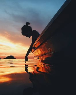 Фото Девушка сидя в лодке, прикасается рукой к воде