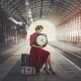 Фото Модель Анна в красном платье, с большими часами сидит на чемоданах перед железнодорожной дорогой, на вокзале. Фотограф Margarita Kareva