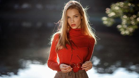 Фото Модель Анна в красной водолазке, с очками в руках, стоит на фоне водоема, фотограф Георгий Чернядьев