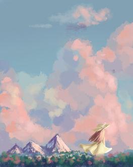 Фото Девочка в шляпе стоит на фоне розовых облаков в поле с цветами