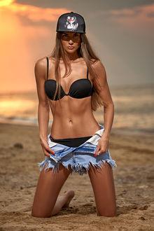 Фото Симпатичная девушка в купальнике, в расстегнутых шортах и бейсболке, стоит на коленках на пляже. Фотограф Vitaliy