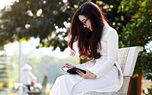 Фото Девушка в белом платье под деревом читает книгу