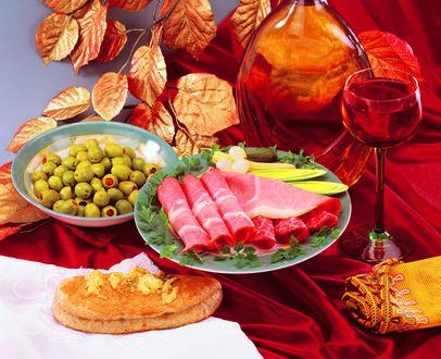 Фото Натюрморт из бокала вина, тарелки с ветчиной и оливками на фоне золотых листьев