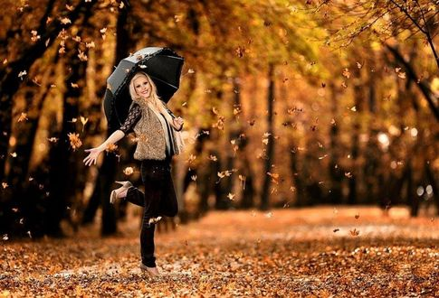 Фото Девушка с зонтиком под листопадом в сквере