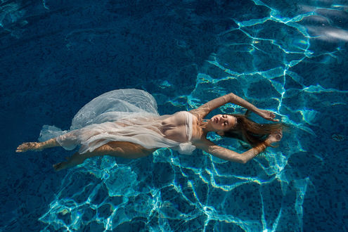 Фото Девушка в белом платье лежит в воде