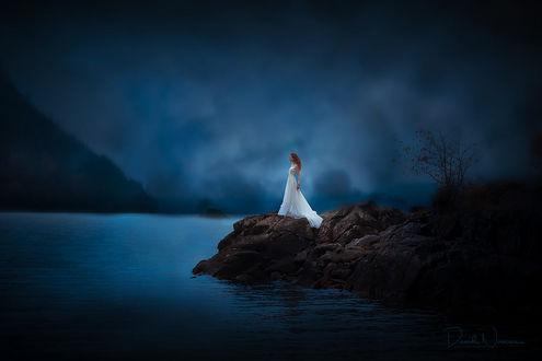 Фото Девушка в длинном белом платье стоит у озера на фоне облачного неба, фотограф David Naman