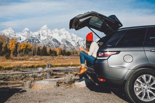 Фото Девушка, сидя в открытом багажнике авто, любуется видом на горы, фотограф Sam Alive