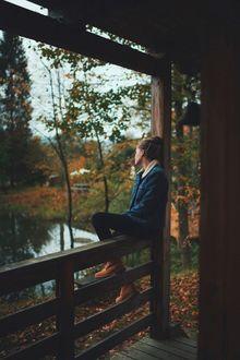 Фото Девушка грустит, сидя на деревянном ограждении крыльца