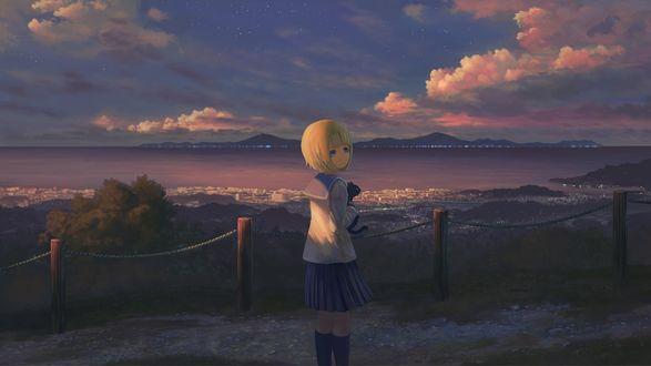 Фото Девочка с котенком на руках стоит на фоне природы
