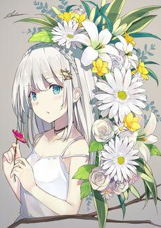 Фото Девушка стоит рядом с цветами и держит цветочек в руке
