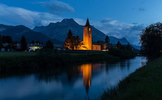 Фото Подсвеченное здание костела у тихой речки в Швейцарии