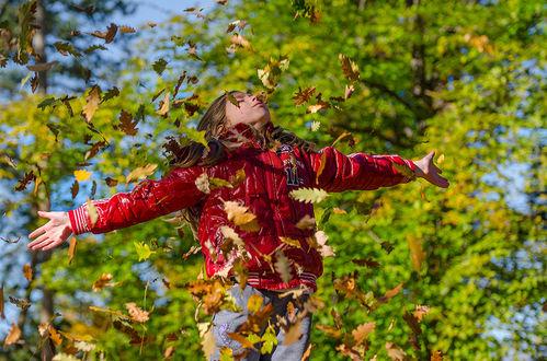 Фото Девочка в красной курточке стоит под листопадом