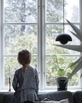 Фото Девочка стоит у окна
