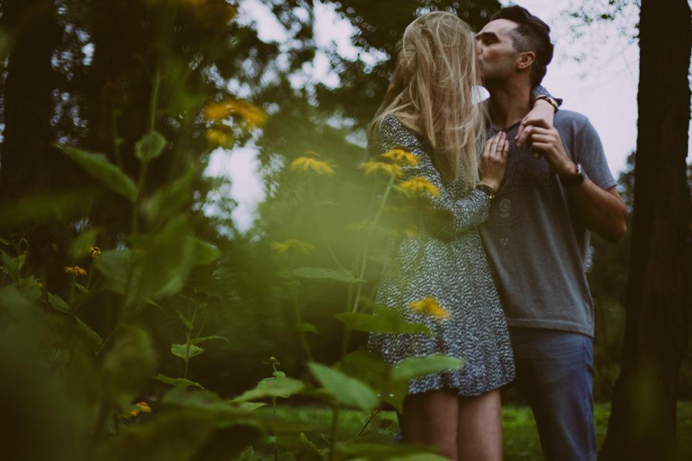 Фото Парень целует девушку, оба стоят за цветущим кустом, фотограф Anita Suchocka