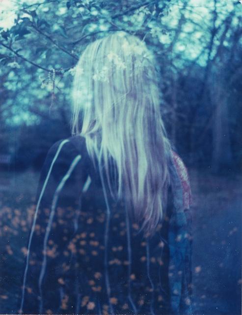 Фото Призрачная девушка со светлыми волосами стоит спиной к зрителю на размытом фоне цветущего сада в предрассветных сумерках