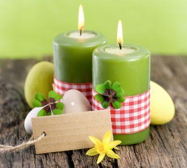 Фото Две горящие зеленые свечи, яички, клевер и желтая орхидея на деревянной поверхности