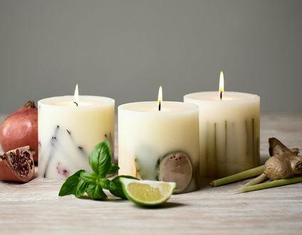 Фото Три горящие свечи, гранат, лайм и мята на сером фоне