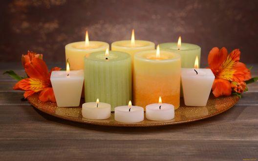 Фото Горящие свечи на круглом подносе с цветами