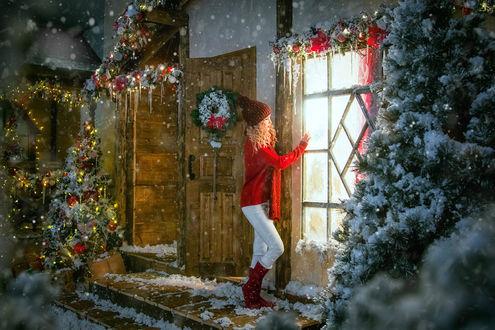 Фото Модель Алина в коричневой вязанной шапочке, красном свитере, шарфе, светлых штанишках и бордовых сапогах стоит у двери дома, украшенного по новогоднему, перед домом растут ели, фотограф Tatiana Antoshina / Татьяна Антошина