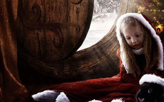 Фото Девочка и кролик в новогоднем одеянии у наряженной елки в сказочном домике на фоне зимней природы