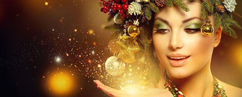 Фото Девушка с новогодней композицией на голове и светящийся пыльцой на руке
