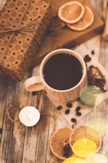 Фото Сушеные апельсины, кружка кофе и подарок на столе под падающим снегом