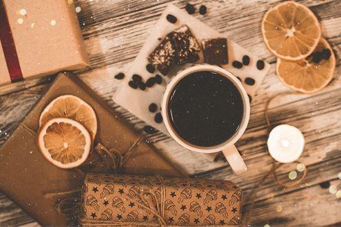 Фото Сушеные апельсины, кружка кофе и подарки на столе под падающим снегом