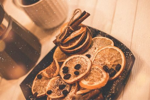 Фото Сушеные апельсины, кружка кофе и корица на столе под падающим снегом