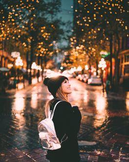 Фото Девушка с рюкзаком стоит но вечерней улице