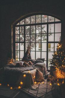 Фото Девушка с парнем лежат на кровати в комнате с новогодней елкой
