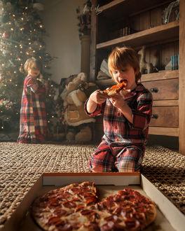 Фото Мальчик кушает рождественскую пиццу, а у елки стоит девочка, фотограф Adrian C. Murray