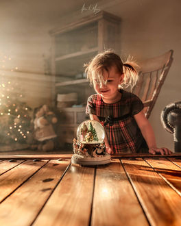 Фото Девочка смотрит на новогоднюю игрушку, фотограф Adrian C. Murray