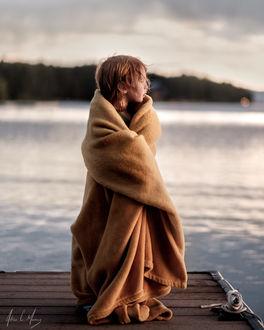 Фото Ребенок, закутанный в плед, стоит на мостике, фотограф Adrian C. Murray