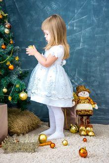 Фото Девочка в белом платье украшает елку
