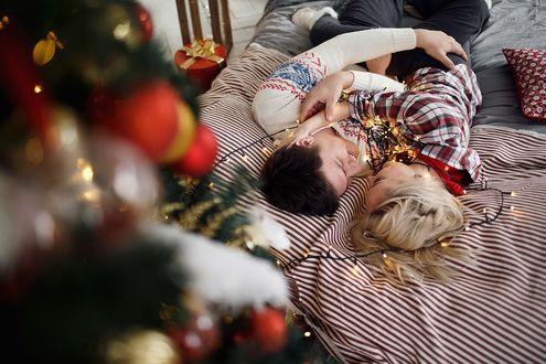 Фото Парень с девушкой на постели, на переднем плане украшенная елка