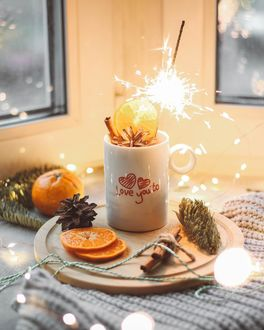 Фото Кружка с надписью Love you tu / Я люблю тебя с бенгальским огоньком внутри, кусочки апельсина, шишка и палочки корицы на деревянной дощечке