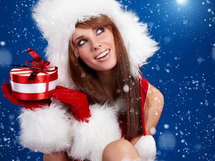 Фото Девушка в новогодней одежде и подарком в руке, на фоне идущего снега