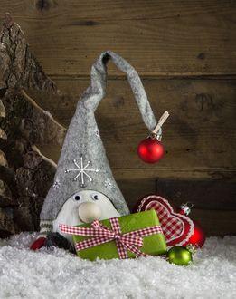 Фото Новогодние игрушки, гном-старичок и подарочек на снегу