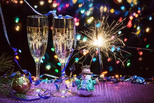 Фото Два бокала с шампанским, новогодние игрушки, елочная ветка на столе, на фоне бенгальского огня и боке, фотограф Igor Sarapulov