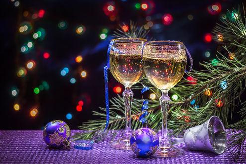 Фото Два бокала с шампанским, новогодние игрушки, елочная ветка на столе, на фоне боке, фотограф Igor Sarapulov