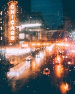 Фото Через мокрое стекло видна улица вечернего города