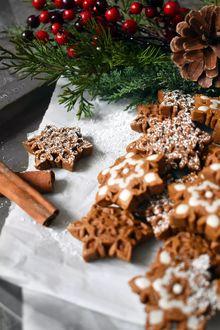 Фото Новогодние печенья в виде снежинок, веточка елового дерева и красные ягоды в букете, by oh hotcakes