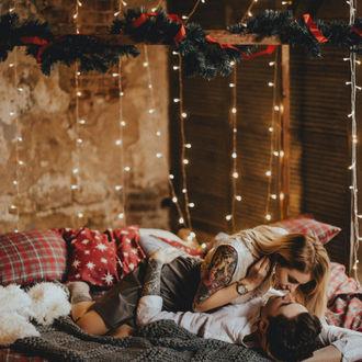 Фото Девушка с парнем лежат на постели в комнате, украшенной к Новому году