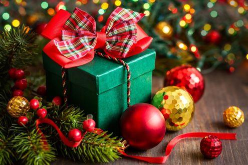 Фото Новогодний подарок и елочные игрушки лежат у елки