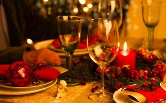 Фото Новогодний стол накрыт для праздничного ужина, на столе бокалы, свечи, новогодние игрушки