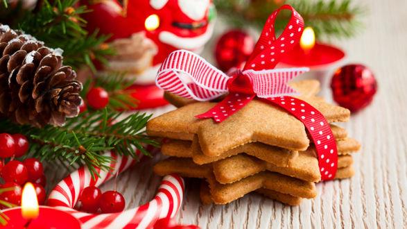 Фото Имбирное новогоднее печенье в форме звездочек, перевязанное красное ленточкой, лежит у елочный украшений, свечей, шишек и веточек ели
