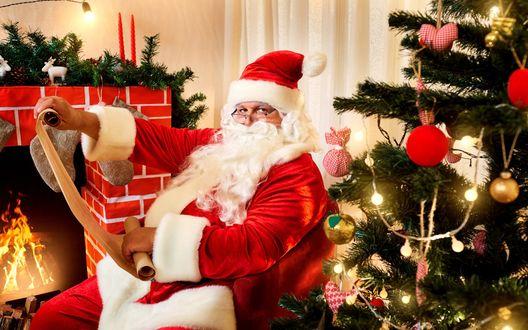 Фото Дед Мороз со списком подарков сидит у елки на фоне камина